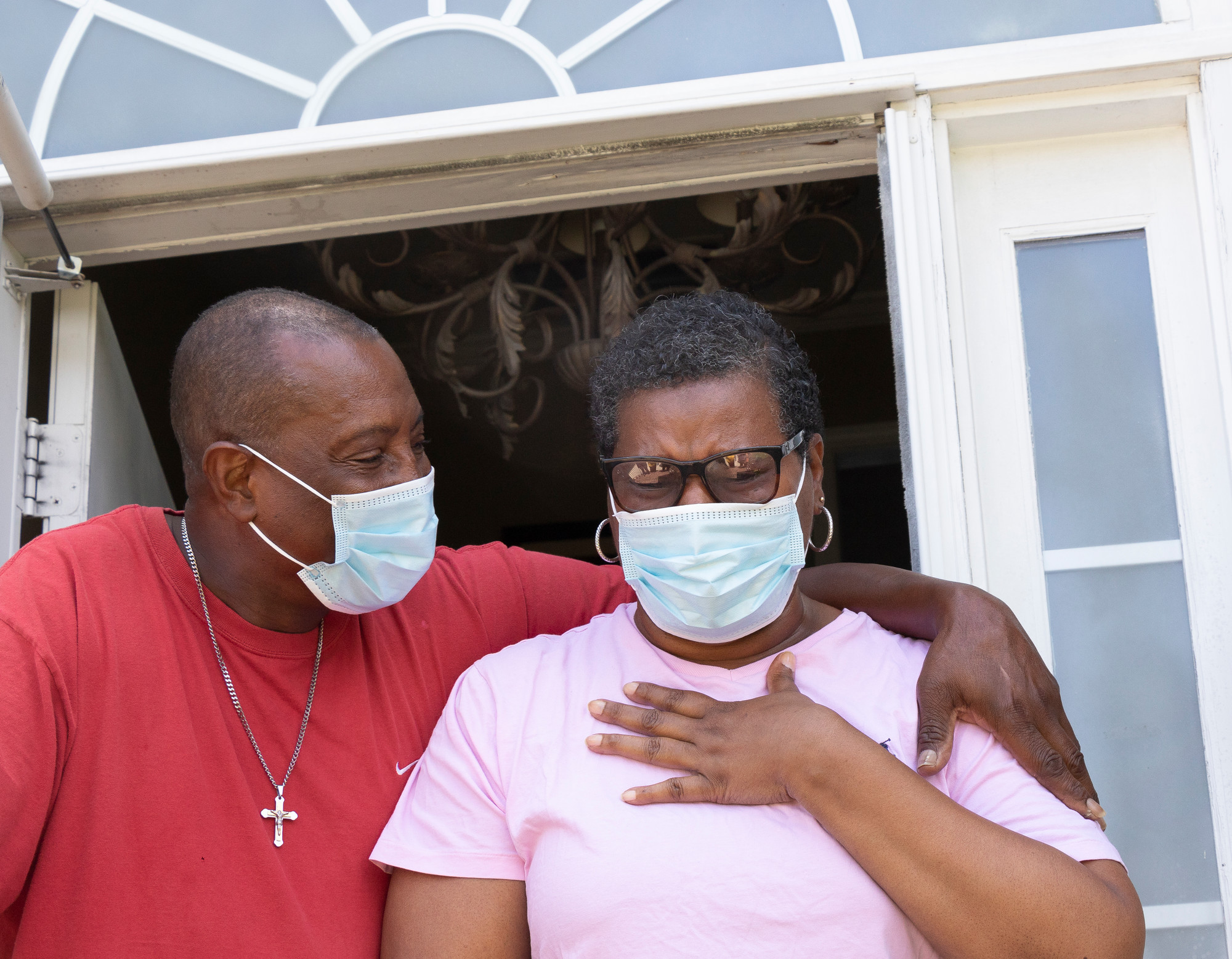 A Black man wraps an arm around a Black woman who is clutching her chest. Both are wearing masks.